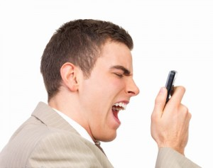 Angry business man screaming at his  cell phone